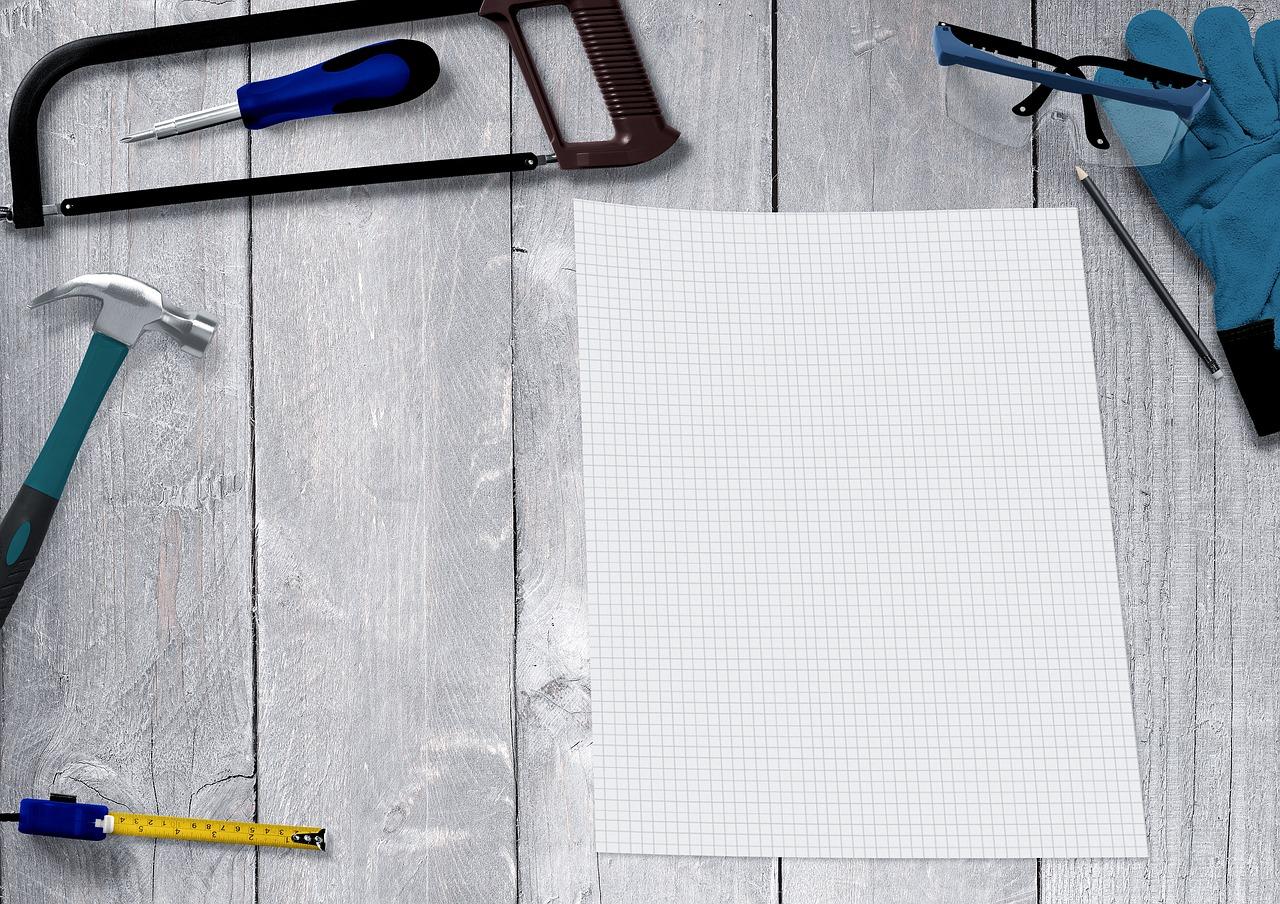 plan maken voor een verbouwing, met een zaag, potlood, bril, schroevendraaier en hamer