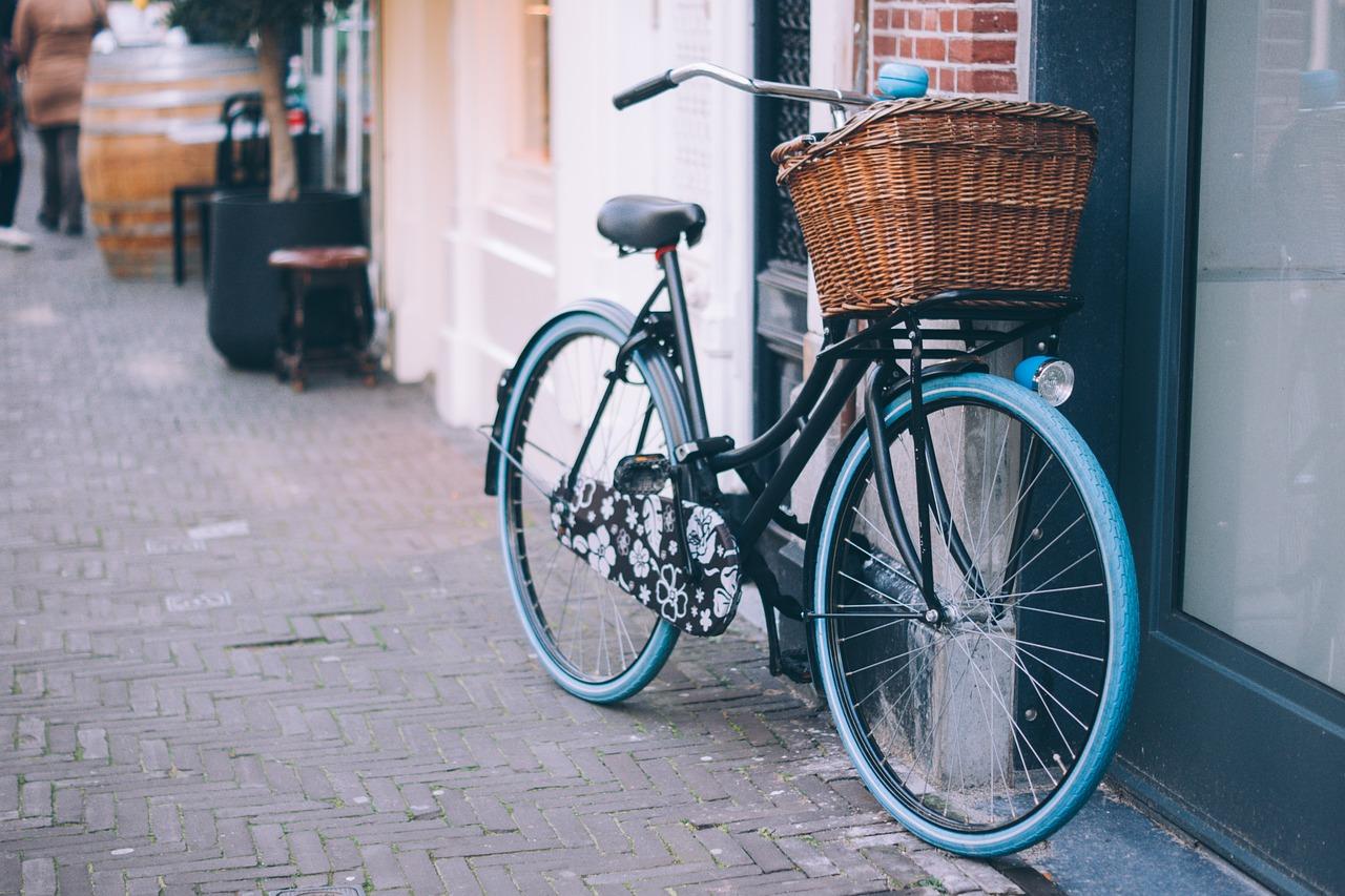 zwarte fiets staat tegen de muur met blauwe banden en mand