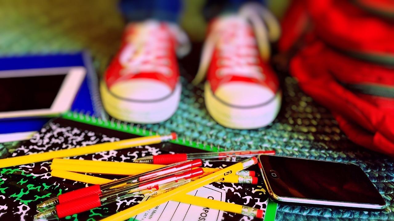nieuw schooljaar, kind met potloden, telefoon en rode gymschoeen